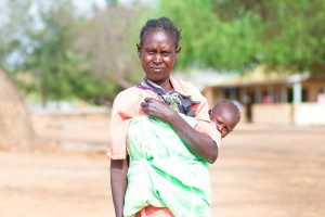 Former leishmaniasis patient standing with her child